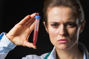 donna del medico che mostra la provetta isolata sul nero foto