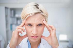 Ritratto di medico che soffre di mal di testa foto