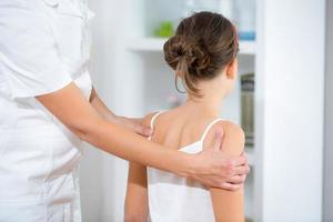 il medico chiropratico regola la ragazza elementare foto