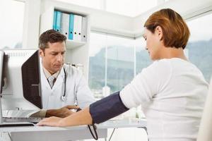 medico che controlla la pressione sanguigna della donna all'ufficio medico foto