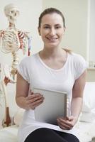 Ritratto di osteopata femmina nella stanza di consultazione con scheda digitale foto