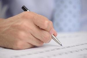 primo piano della mano dell'uomo d'affari con la penna foto