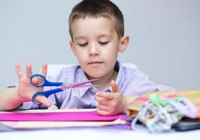 il ragazzo sta tagliando la carta usando le forbici foto