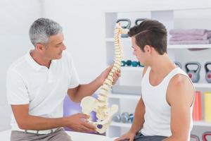 medico che mostra la colonna vertebrale anatomica al suo paziente foto