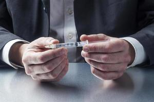 uomo d'affari in possesso di una siringa piena di droga o vaccino foto