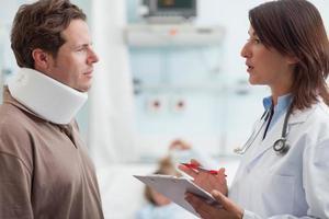 medico che parla con paziente maschio con un collare