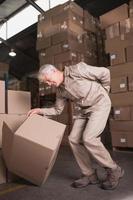 lavoratore con mal di schiena durante il sollevamento della scatola in magazzino foto