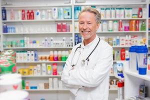 farmacista in camice da laboratorio con stetoscopio e braccia incrociate foto
