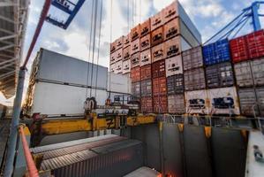 la gru portuale solleva il container durante l'operazione di carico