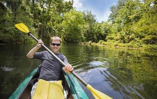 uomo felice kayak lungo il bellissimo fiume nella giungla foto