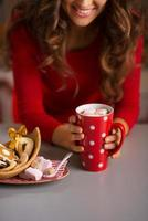 donna che mangia tazza di cioccolata calda e dolci natalizi. avvicinamento