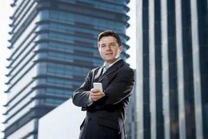 Ritratto corporativo di giovane uomo d'affari attraente con il telefono cellulare all'aperto foto