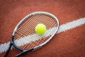 racchetta da tennis e palla in campo foto