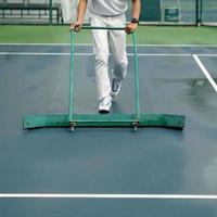 personale di pulizia che asciuga il campo da tennis dopo la pioggia