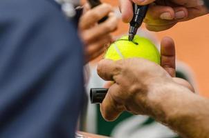 il giocatore di tennis firma l'autografo dopo la vittoria foto