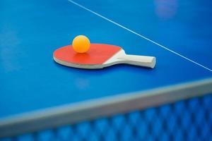 racchetta da ping pong e palla e rete sul tavolo da ping pong verticale foto