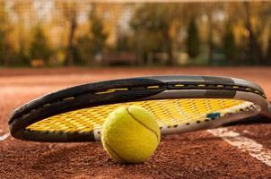 concetto di tennis con racchetta e palla sul campo in terra battuta foto