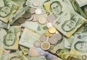 la nota di baht tailandese ed i soldi della moneta visualizzano come fondo foto