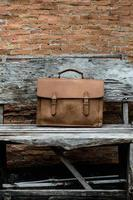 borsa per laptop in pelle marrone corporativa sulla vecchia sedia di legno foto