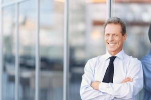 uomo d'affari piacevole che sta l'edificio per uffici vicino foto