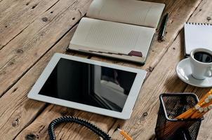 tablet con un taccuino e una tazza di caffè nero foto
