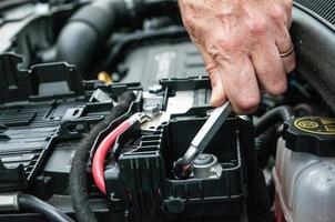 stringendo a mano un morsetto in un motore di automobile foto