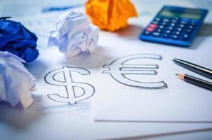 mano disegnando un segno di dollaro e simbolo dell'euro foto