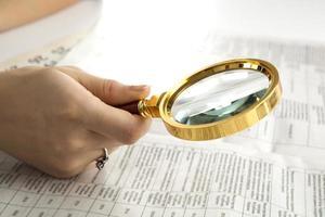il lavoratore esamina un testo della lente d'ingrandimento foto