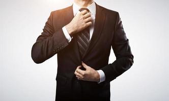 uomo d'affari regola la sua cravatta foto