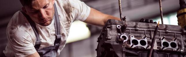 meccanico del garage che ripara motore foto