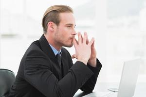uomo d'affari concentrato in tuta utilizzando il computer portatile foto