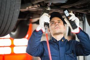 meccanico che ripara un'auto foto