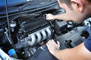 meccanico che controlla il motore di automobile foto