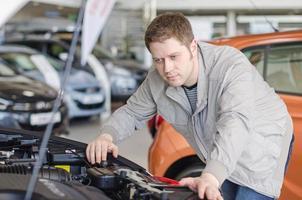 uomo che esamina la nuova auto presso la concessionaria. foto