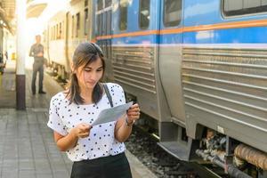 la donna esamina un biglietto prima di salire sul treno sul binario.