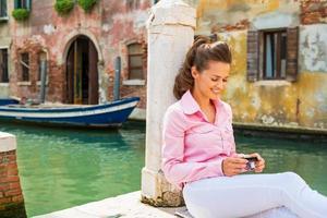 giovane donna sorridente che si siede sulla via a Venezia foto