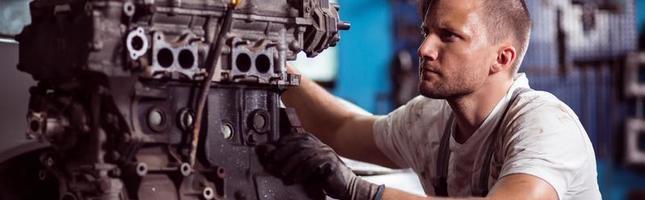riparatore che ripara il motore di automobile