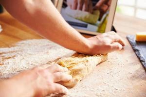 persona che segue la ricetta della pizza utilizzando l'app su tavoletta digitale foto