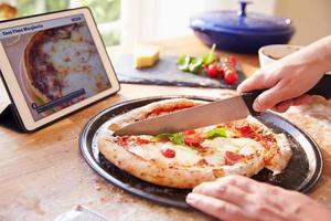 persona che segue la ricetta della pizza utilizzando l'app su tavoletta digitale