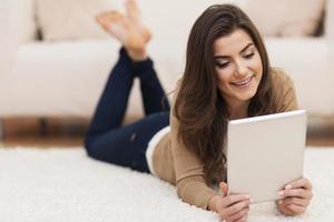 donna felice sul tappeto utilizzando la tavoletta digitale foto