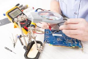 il tecnico controlla il pcb con un multimetro digitale foto
