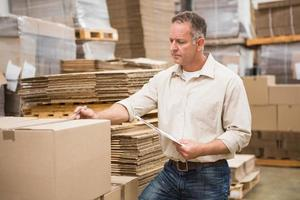 magazziniere che controlla la sua lista sulla lavagna per appunti foto