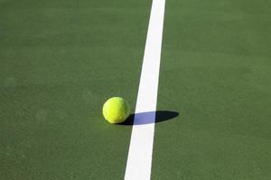 palla da tennis accanto alla linea bianca da vicino foto