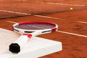 racchetta da tennis sul tavolo, campo in terra battuta, rete e palla foto