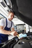 meccanico al lavoro che controlla il livello dell'olio sul motore di un'auto foto