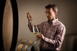 Vinaio che preleva campione di vino bianco in cantina. foto