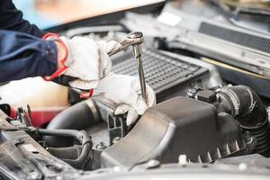 meccanico che lavora su un'auto nel suo garage foto