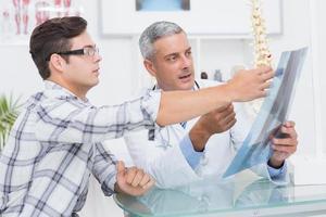 medico che mostra i raggi x al suo paziente foto