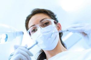 dentista in maschera che tiene specchio ad angolo e trapano foto