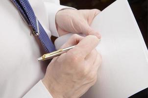 foglio di carta e penna della tenuta dell'uomo d'affari foto